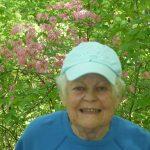 87 year woman with in blue shirt & light blue ball cap w/ pink Azaleas behind